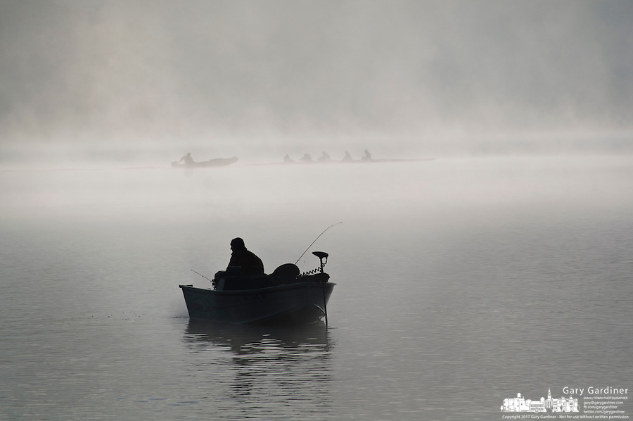 A fisherman steers his boat across fog shrouded Hoover Reservoir as a rowing team practices as the sun begins to rise on a Saturday morning.