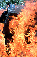 Police officers attending a riot. They have been attacked with petrol bombs and have to walk through the flames to arrest the rioters. They are wearing flame proof jumpsuits and riot gear including helmet, shields and batons. This image may only be used to portray the subject in a positive manner..©shoutpictures.com..john@shoutpictures.com