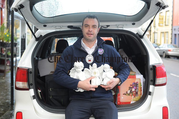 Salesman David Conboy waits at the back of his van for a shower to clear before making a delivery of his miniature Angels in Kilrush. Photograph by John Kelly.