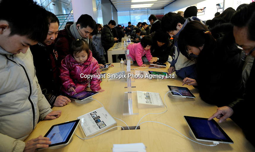 Customers trying out Apple iPad in the Apple Store in Beijing, China. China Realtime Report says that Chinese Apple Stores are big business for the company, averaging 40,000 visitors per day that's more than four times the traffic of Apple's U.S. stores, its stores brought in a reported US$2.6 billion last quarter, the best numbers from any of their stores worldwide. By 2012, Apple will meet its goal 25 China Apple stores..