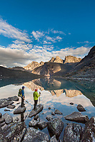 Hikers view East and West Maiden and Camel peaks as they reflect in a mountain lake in the Arrigetch Peaks, Gates of the Arctic National Park, Alaska.