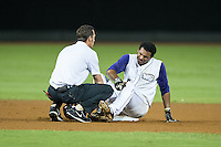 Winston-Salem Dash trainer Josh Fallin checks on the left ankle of Cleuluis Rondon (5) after he twisted it at second base during the game against the Myrtle Beach Pelicans at BB&T Ballpark on August 20, 2015 in Winston-Salem, North Carolina.  The Dash defeated the Pelicans 5-4 on a walk-off wild pitch in the bottom of the 9th inning.  (Brian Westerholt/Four Seam Images)