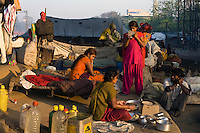 A family rouse themselves and a girl checks her appearance in a mirror on waste ground beneath a flyover near Okhla station.
