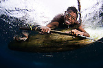 Local children swimming from small outrigger canoes using home made goggles, Alor Island, Nusa Tenggara, Indonesia, Pacific Ocean