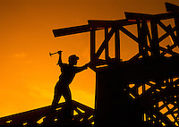 Construction worker silhouetted against sunset