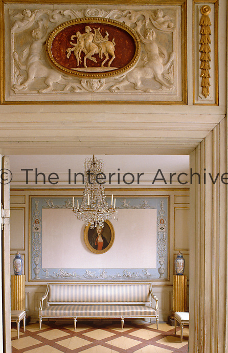 A carved relief hangs over the doorway leading to a small sitting room furnished with a crystal chandelier and a dainty canape
