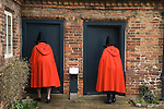 Old Ladies of Castle Rising. The Hospital of the Holy and Undivided Trinity Almshouses, Castle Rising, Norfolk, England 2007. Founders Day. The ladies wear traditional red cloaks and pointed black hats.