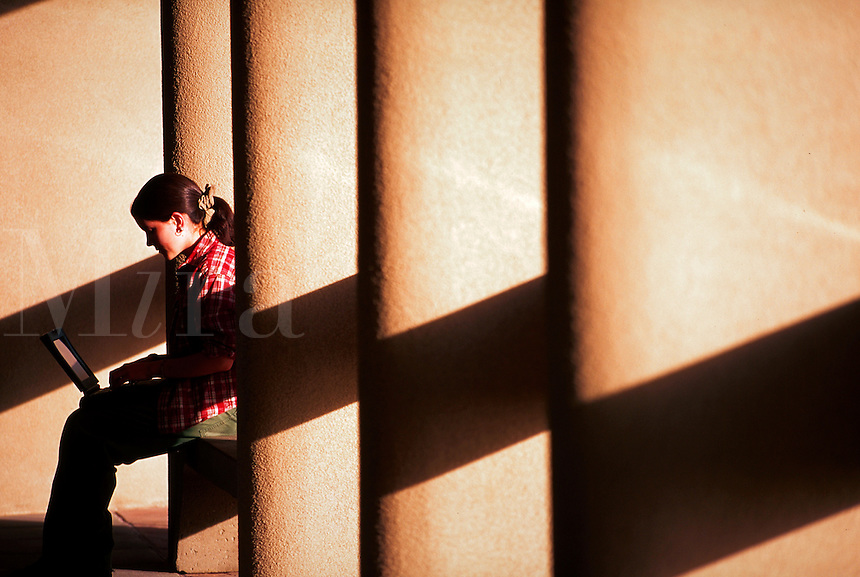 A girl with a laptop computer sits in between pillars with patterns of shade.