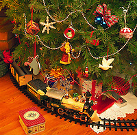 Detail of a Christmas tree with a toy train running underneath.