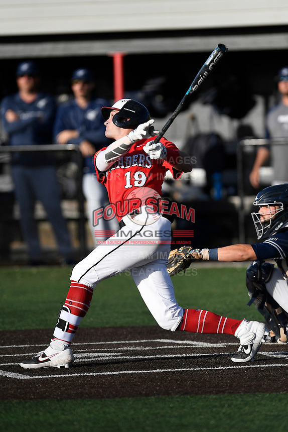 Center fielder John Senter (19) of the North Greenville Crusaders bats in a game against the Palm Beach Atlantic Sailfish on Monday, February 25, 2019, at Ashmore Park in Tigerville, South Carolina. The catcher is Marcos Perez. Palm Beach won, 7-5. (Tom Priddy/Four Seam Images)