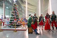 A band dressed in santa hats sings Christmas carols in the terminal at Indira Gandhi International Airport in Delhi, , on Mon., Dec. 24, 2018.