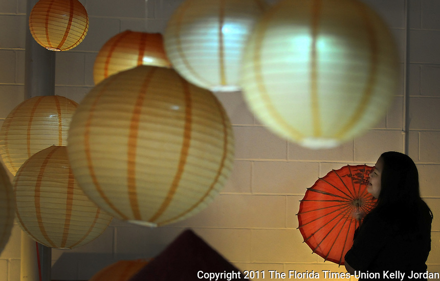 """Kelly.Jordan@jacksonville.com--011512--The Vietnamese Association of Jacksonville marked Vietnam's largest and most important festival, known as """"Tet, """" Sunday at the Jacksonville Fairgrounds. A visitor to the popular festival checks out a display of traditional paper lanterns and umbrellas during the event which featured a fasjhion show, traditional food and music. Mayor Alvin Brown also attended the event.(The Florida Times-Union, Kelly Jordan)"""