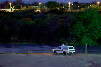 Border Patrol officer parked next to Rio Grande guarding against illegal crossing. Street lights across the river are in Nuevo Laredo, Mexico. Laredo Texas USA.