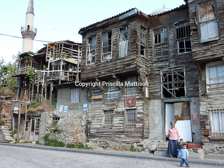 Istanbul, Turkey - September 23, 2009:  A woman and two boys stand in front of a traditional wooden house near a minaret of the Zeyrek Mosque in Unkapani.