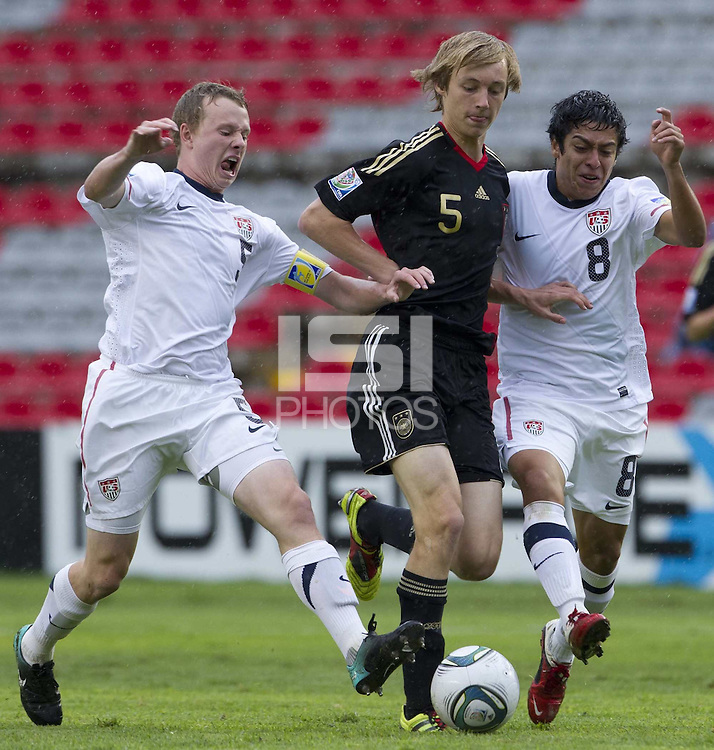 .Action photo of Nico Perrey (C) of Germany and Matthew Dunn (L) Esteban Rodriguez (R) of USA, during game of the FIFA Under 17 World Cup game, held at Queretaro.