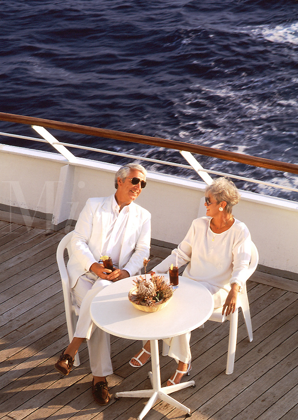 Mature couple enjoying drinks on cruise ship deck