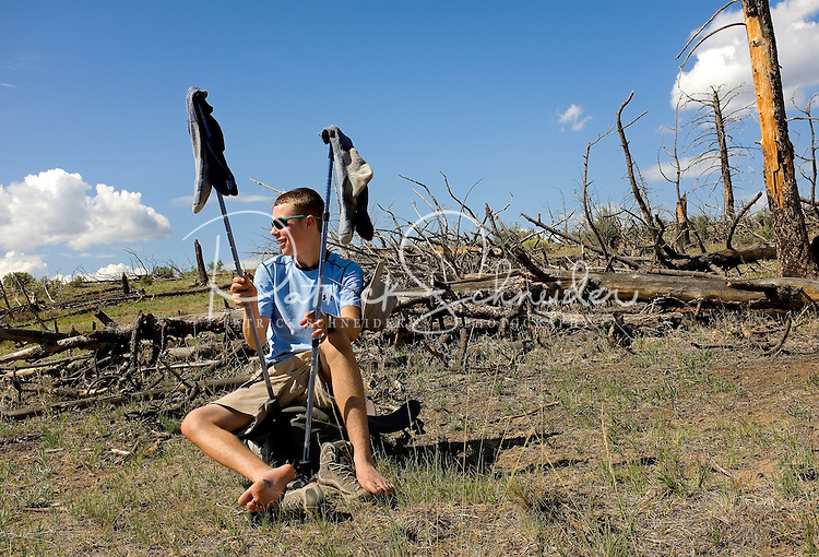 Photo story of Philmont Scout Ranch in Cimarron, New Mexico, taken during a Boy Scout Troop backpack trip in the summer of 2013. Photo is part of a comprehensive picture package which shows in-depth photography of a BSA Ventures crew on a trek.  In this photo BSA Venture Crew Scouts take a break from hiking to to dry out his wet socks before continuing to climb in the backcountry at Philmont Scout Ranch.   <br /> <br /> The  Photo by travel photograph: PatrickschneiderPhoto.com