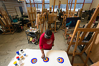 Donna McDonald pours primary colors onto canvases to form the background for her next painting during Professor Tom Chung's Intermediate Painting (ART A313) class in UAA's Fine Arts Building.