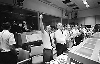 """04/17/1970 File Photo - Three of the four Apollo 13 Flight Directors applaud the successful splashdown of the Command Module """"Odyssey"""" while Dr. Robert R. Gilruth, Director, Manned Spacecraft Center (MSC), and Dr. Christopher C. Kraft Jr., MSC Deputy Director, light up cigars (upper left). The Flight Directors are from left to right: Gerald D. Griffin, Eugene F. Kranz and Glynn S. Lunney. Apollo 13 crew members, astronauts James A. Lovell Jr., Commander; John L. Swigert Jr., Command Module pilot, and Fred W. Haise Jr., Lunar Module pilot, splashed down at 12:07:44 (CST) in the South Pacific Ocean, approximately four miles from the Apollo 13 prime recovery ship, the U.S.S. Iwo Jima."""