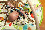 10 day old newborn baby boy closeup lying on back looking at hanging toys re-reaching with hand