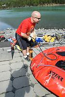 Nick Lynch pumps up a raft at Cooper Landing along the Kenai River.