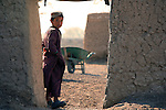 A boy stands in a doorway, watching US troops as they talk to an elder in the village of Mama Karez in Maiwand district, Kandahar province, Afghanistan. Soldiers with Company A, 2nd Battalion, 2nd Infantry Regiment have recently built a nearby camp in an effort to disrupt Taliban activity in the area. Dec. 29, 2008 DREW BROWN/STARS AND STRIPES