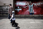 A child dressed in the typical clothing of Madrid 'chulapo' with his father walking in front of the Atletico de Madrid's store at Vicente Calderon Studium in Madrid. May 14, 2014. (ALTERPHOTOS/Caro Marin) Real Madrid and Atletico de Madrid will play the final of the Champions League in Lisbon the next 24th of May. It is the first time in the final of the Champions League that two teams are from the same city.