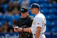 Michigan Wolverines head coach Erik Bakich (23) makes a change with umpire Mark Spicer during a game against Army West Point on February 18, 2018 at Tradition Field in St. Lucie, Florida.  Michigan defeated Army 7-3.  (Mike Janes/Four Seam Images)