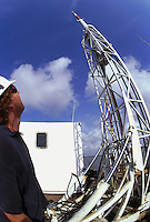 Workman lowering raising a recording vessel mast tower to record seismic data in the search for oil and gas. Louisiana, Lake Salvador.