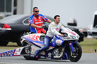 Mar. 10, 2012; Gainesville, FL, USA; NHRA pro stock motorcycle rider Hector Arana Jr is pushed back to the pits by a crew member during qualifying for the Gatornationals at Auto Plus Raceway at Gainesville. Mandatory Credit: Mark J. Rebilas-