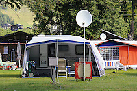 Tents and mobile home and sat dish in Alpine camping