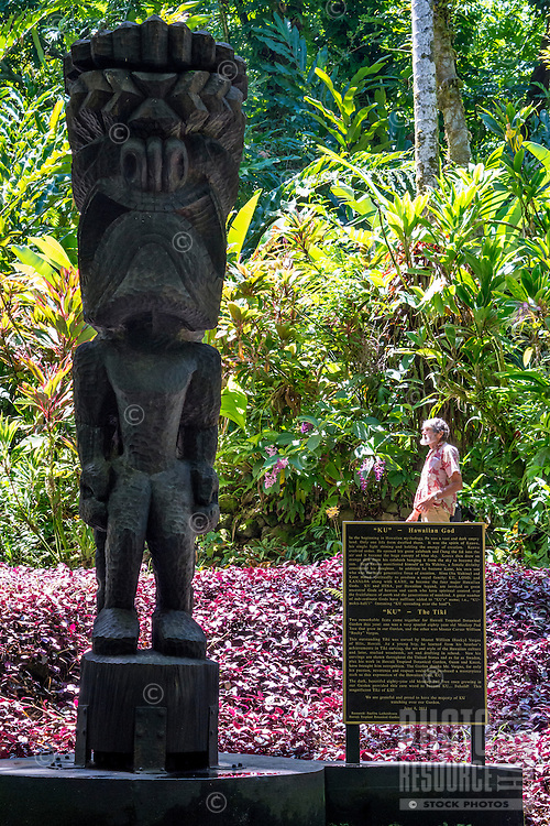 "A man stands behind the sign for the carved wooden tiki of Hawaiian god ""KU"" at the Hawaii Tropical Botanical Garden in Papa'ikou (near Hilo), Big Island of Hawai'i."
