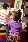 Education preschool 3-4 year old indoor physical activity boy and girl throwing small balls through holes in board