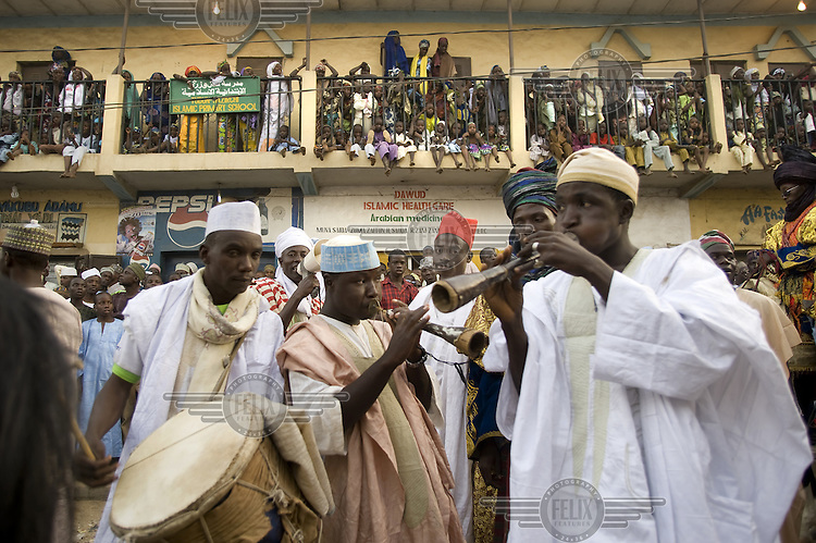 A group of musicians play in the street watched, from every vantage point, by spectators at the Kano Durbar. This spectactular parade of horsemen, musicians and people celebrates the Muslim festival of Eid al-Adha and is the time for the populace to pledge their loyalty to their traditional ruler, the Emir of Kano.