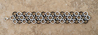 """A chainmail bracelet made by Michelle in a Japanese 12-in-2 pattern from 18 gauge 1/4"""" black and white anodized aluminum rings with 20 gauge 1/8"""" bright aluminum rings as connectors.  Taken on a concrete floor for a rugged background."""