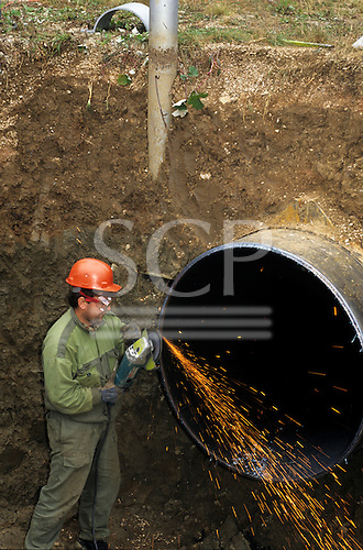 Slovakia. Man wearing an orange hard hat in an excavated hole working on a large gas pipeline using an angle grinder.