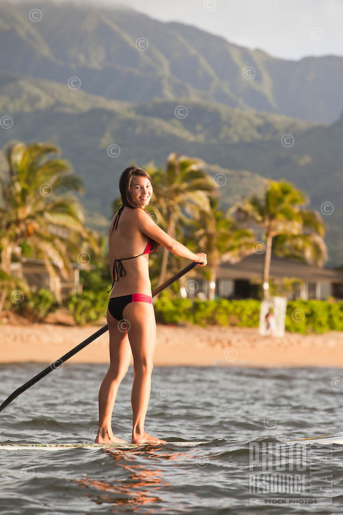 Woman standup paddling off the coast of the North Shore of Oahu
