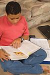 15 year old teenage boy at home doing homework looking at school books Hispanic Puerto Rican