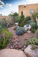 Dry stream bed drainage above water storage pumice wicks in David Salman New Mexico garden with roof gutters draining into courtyard