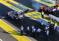 Aug 15, 2014; Brainerd, MN, USA; Crew members look on as NHRA funny car driver Robert Hight (left) races alongside Bob Bode during qualifying for the Lucas Oil Nationals at Brainerd International Raceway. Mandatory Credit: Mark J. Rebilas-USA TODAY Sports