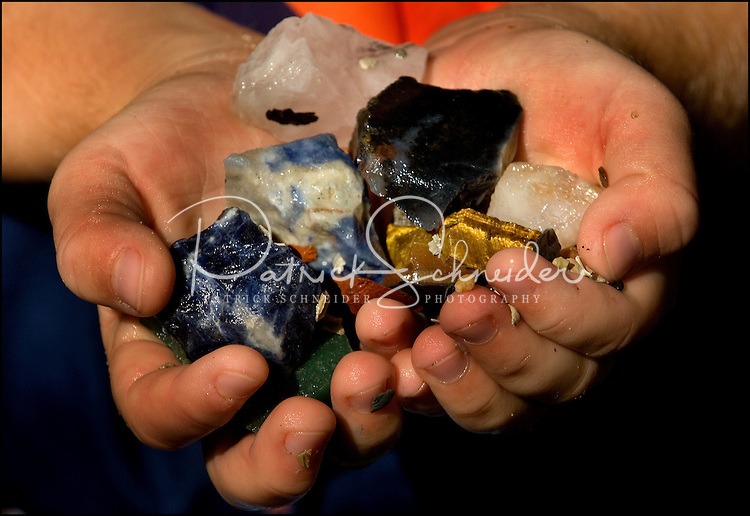 A child's hands hold a handful of colorful rocks, gems and crystals uncovered while mining for gems in the Carolinas.