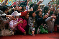 Shoppers reach towards a jewelry merchant in hopes of receiving a free necklace or a discount on other jewelry in Kunming, Yunnan, China.