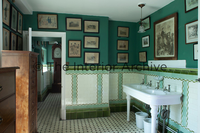 Framed, Victorian illustrations hang from the walls of this green and white tiled bathroom