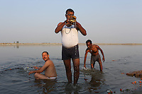 Men bathing and worshipping in the Ganges River, in the city of Kanpur.