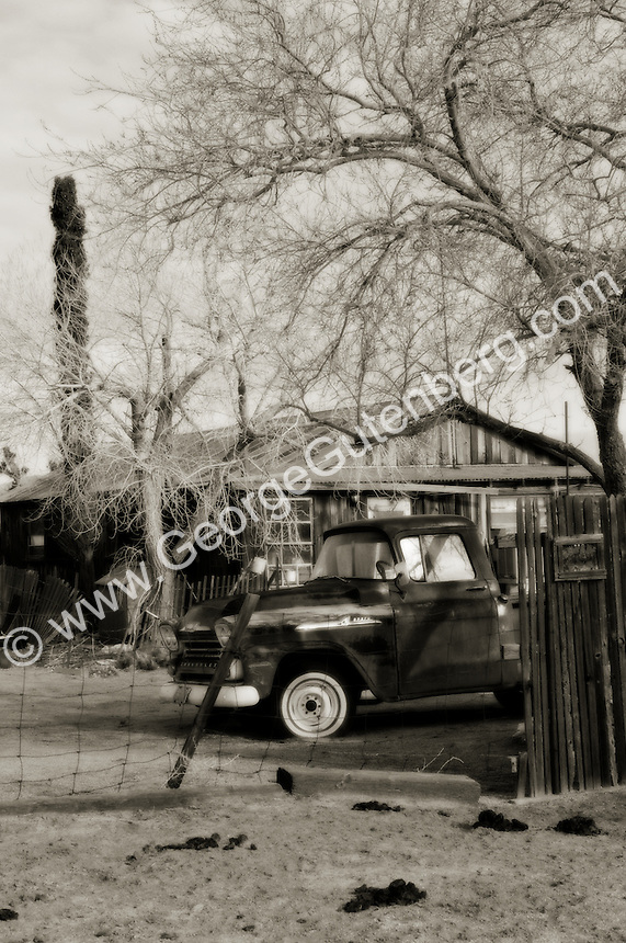 Black and white photo of old truck outside old ranch house