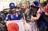 MOSCOW, RUSSIA - June 26, 2018: Japanese fans pose for a photograph with some Russians on Nikolskaya Street during the 2018 FIFA World Cup. The street was a crossroads for foreign soccer fans during the World Cup in Russia.