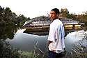 Maverick Ancar, a football player for Port Sulfur High School, looks at his home floating in a canal, Aug. 30, 2006.<br /> (Cheryl Gerber for New York Times)
