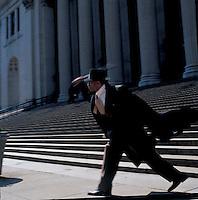 Man in suit on steps swinging nightstick