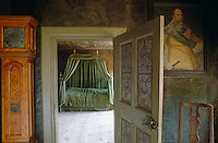 View through a painted doorway into a bedroom with a green canopied bed