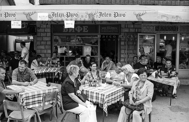Festival di trombe e ottoni di Guca (Cacak). Gente seduta ai tavoli esterni di un ristorante bar --- Trumpet festival of Guca (Cacak). People sitting at the tables outside of a bar restaurant